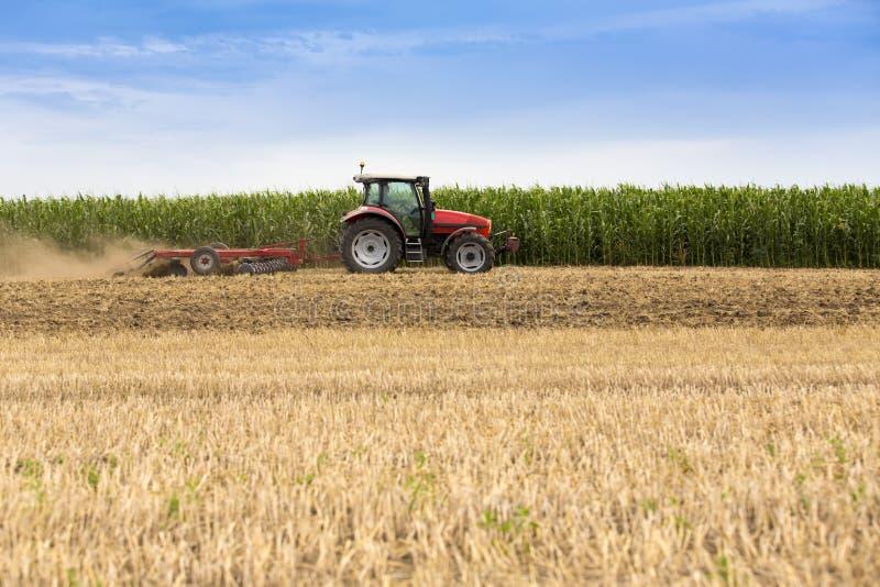 Traktor, der Weizenstoppelfeld, Ernterückstände kultiviert lizenzfreie stockfotos