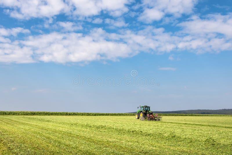 Traktor i grönt fält under blå himmel med moln arkivfoton