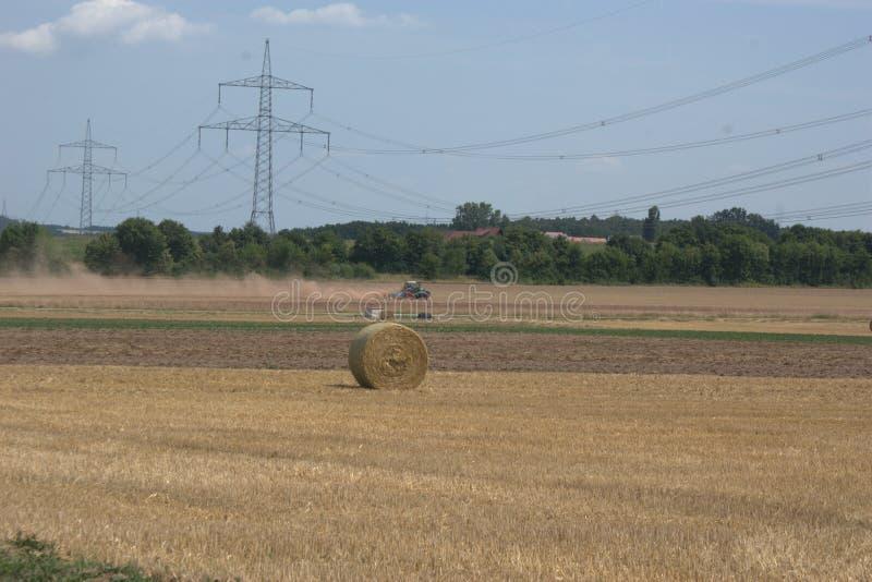 Traktor im Abstand, ein Feld nach der Sommerernte eggend und oben werfen Staubwolken, mit Strohballen im Vorderteil stockbild