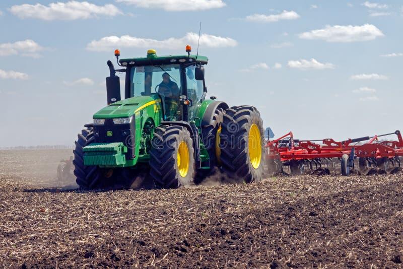 Traktor med den skuggade planteren på fältet arkivbilder