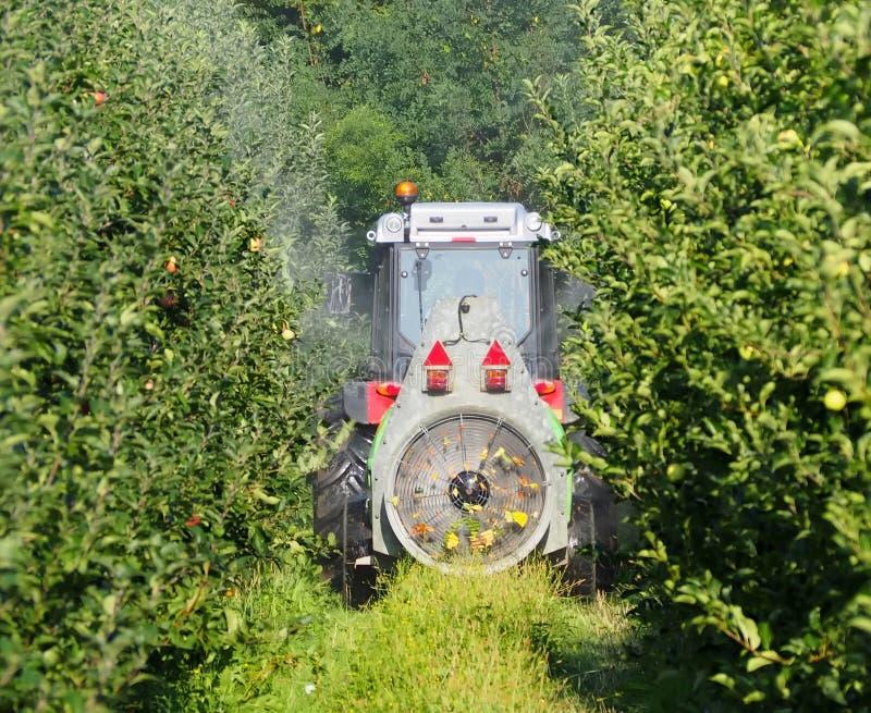 Traktor med en jordbruks- sprejaremaskin med den stora fanen, spridningbekämpningsmedel i en äpplefruktträdgård arkivfoton