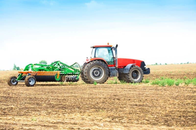 Traktor med ett harv arkivfoto