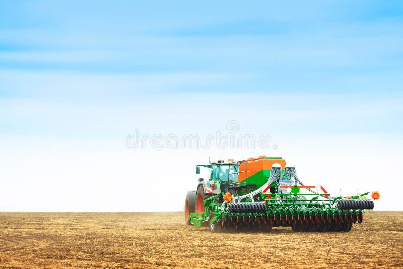 Traktor med ett harv arkivbild
