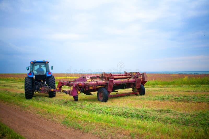Traktor med gräsklippningsmaskinen i fältet av sainfoin och alfalfa royaltyfria bilder