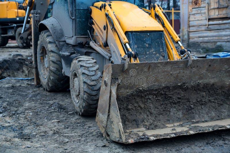 Traktor med skopan i gyttja på roadworksplatsen arkivbild