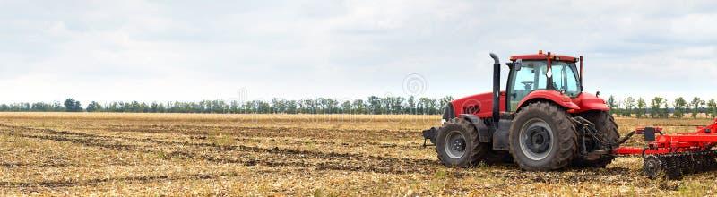 Traktor mit dem Pflug, der auf dem Gebiet arbeitet lizenzfreies stockfoto