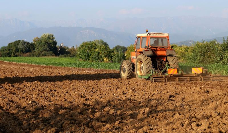 Traktor mit einem geschleppten Pflug schließt das Pflügen des Feldes vor der Herbstsaat ab stockbild