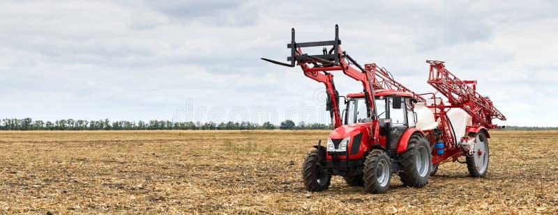 Traktor mit einem Sprüher für landwirtschaftliche Chemie mit einem Feld stockfotos