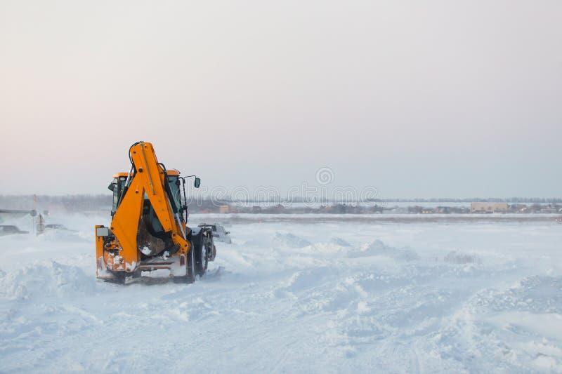 Traktor mit Schneepflug bei der Arbeit lizenzfreie stockbilder