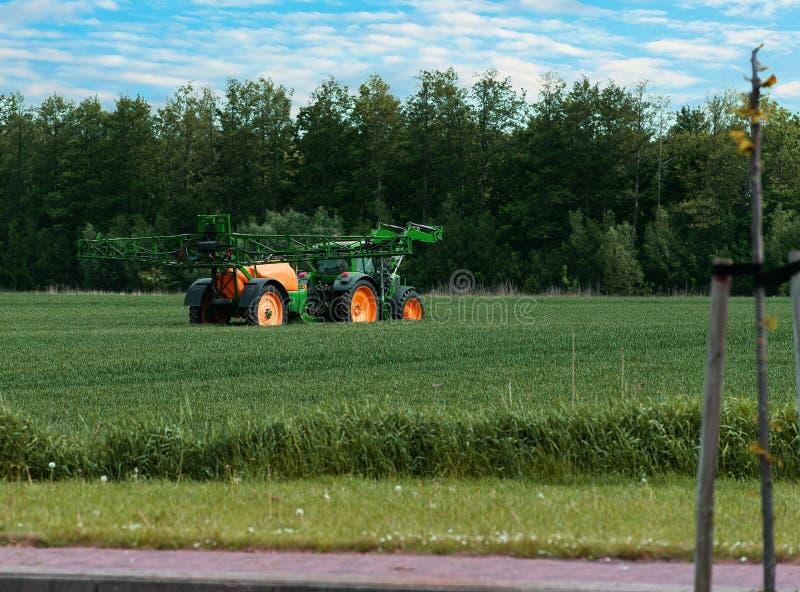 Traktor mit Sprüher während der Anwendung von Schädlingsbekämpfungsmitteln stockbilder