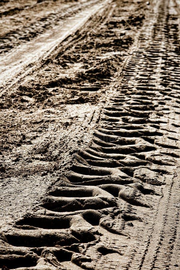 Traktor-Rad-Gummireifen-Spuren im trockenen Schlamm auf Schotterweg lizenzfreies stockfoto