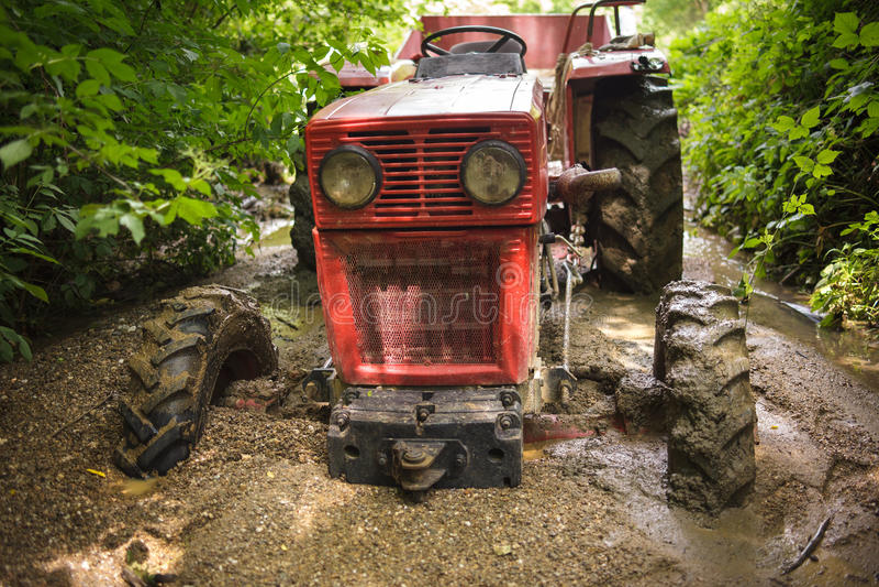 Traktor som klibbas i gyttjan royaltyfri foto