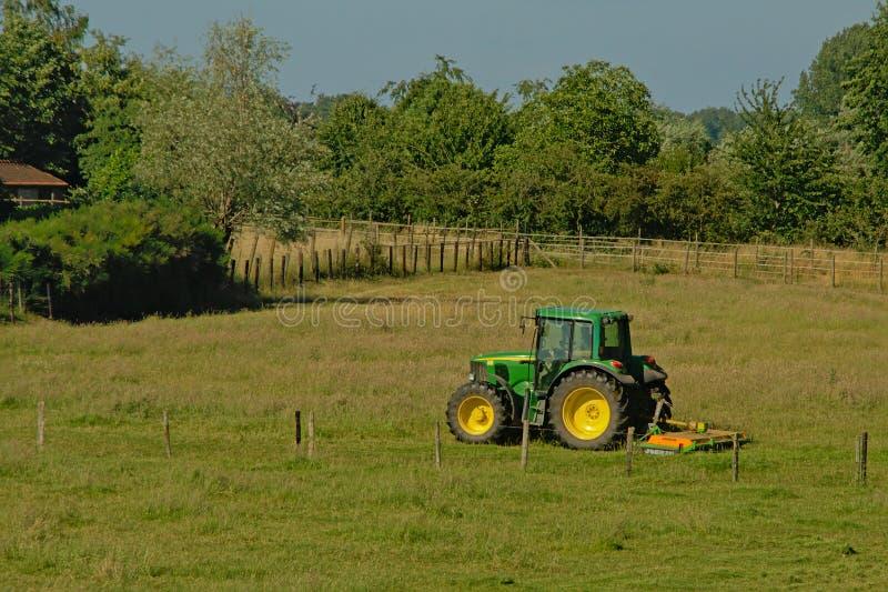 Traktor som mejar en äng i Kalkense Meersen naturreerve, Flanders, Belgien arkivfoton