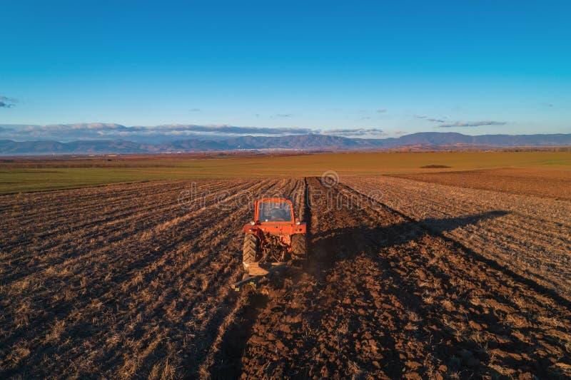 Traktor som odlar fältet på våren, flyg- sikt royaltyfri foto