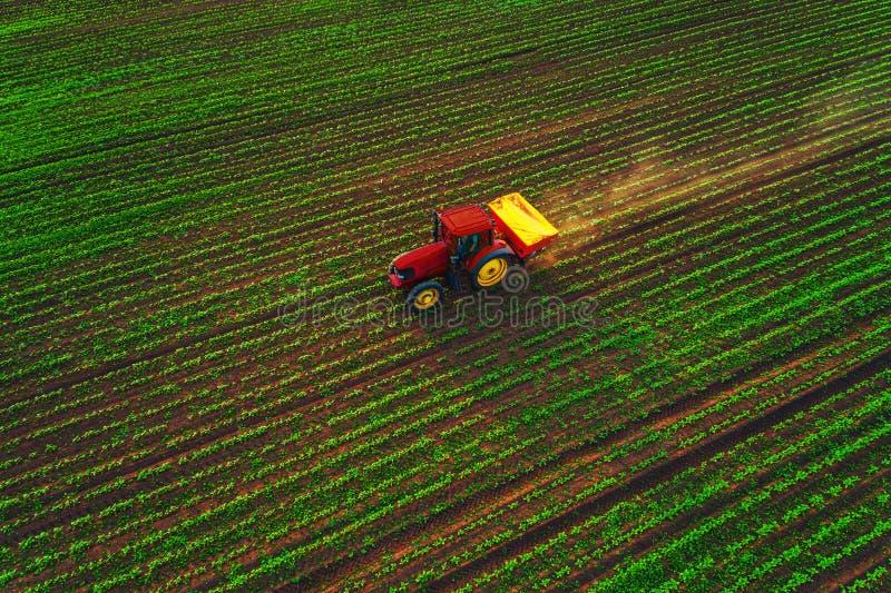 Traktor som odlar f?ltet p? v?ren, flyg- solnedg?ngsikt arkivfoton