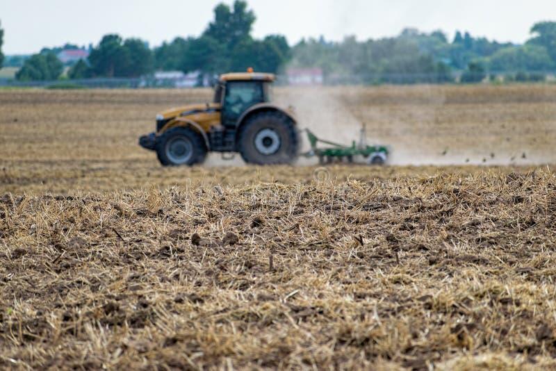 Traktor som odlar f?ltet arkivbilder