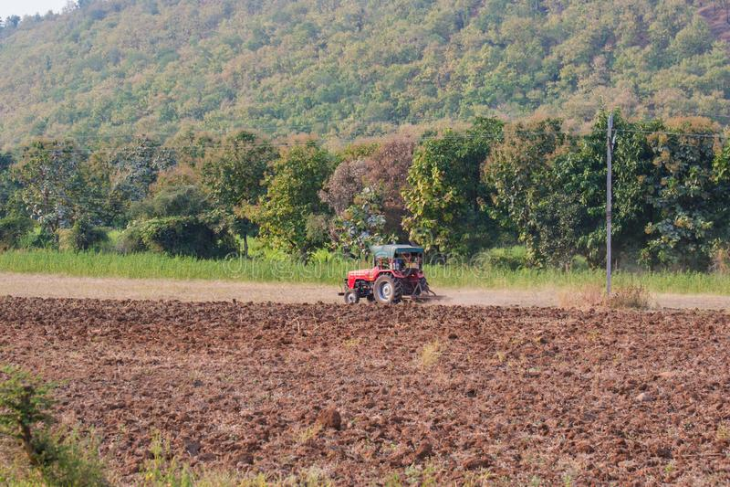 Traktor som plöjer det åkerbruka fältet på Forest Land royaltyfria bilder