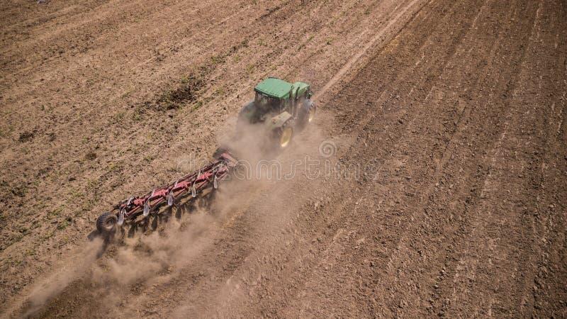 traktor som plogar den b?sta sikten f?r f?lt, flygfotografering med surret arkivbild