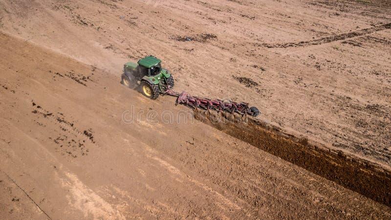 traktor som plogar den b?sta sikten f?r f?lt, flygfotografering med surret royaltyfria foton