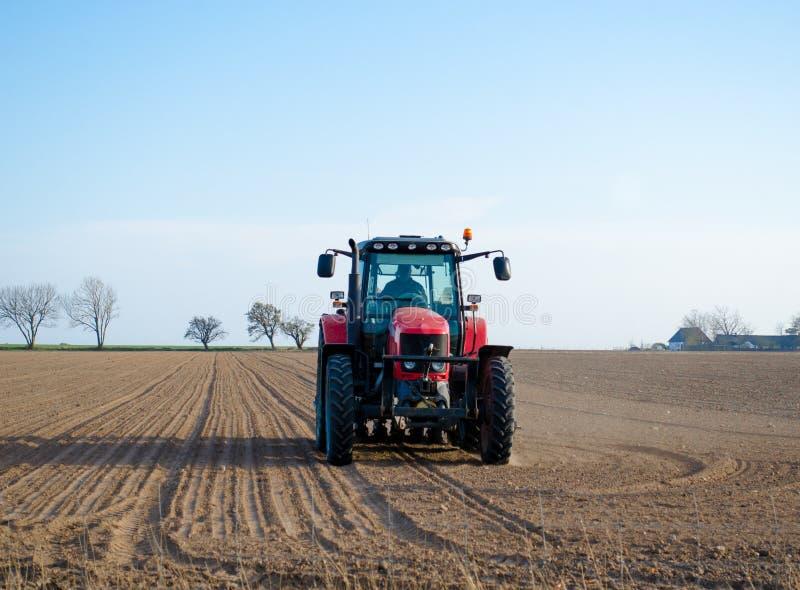 Traktor som plogar fält arkivfoton
