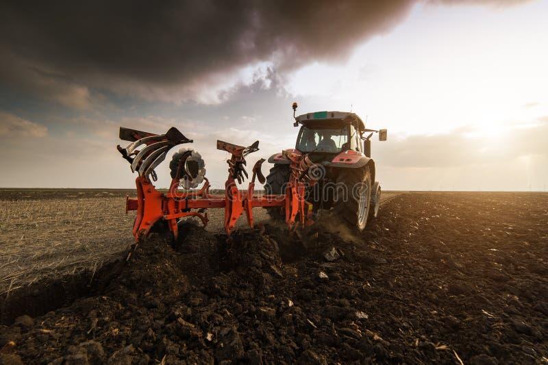 Traktor som plogar fält - förbereda land för att så i höst arkivfoto