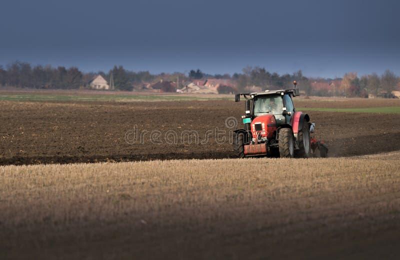 Traktor som plogar fält - förbereda land för att så i höst royaltyfri bild