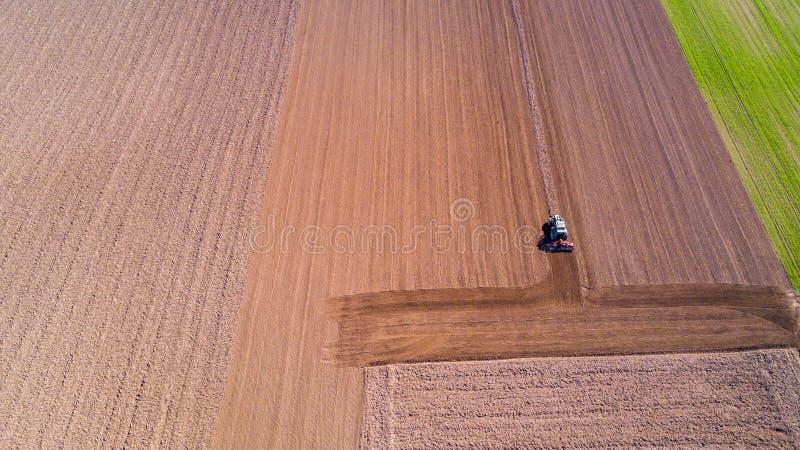 Traktor som plogar fälten, den flyg- sikten, ploga, så, skördjordbruket och lantbruket, aktion royaltyfri bild
