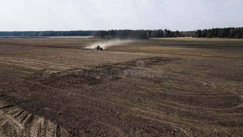 Traktor som plogar fältflygfotografering royaltyfri fotografi