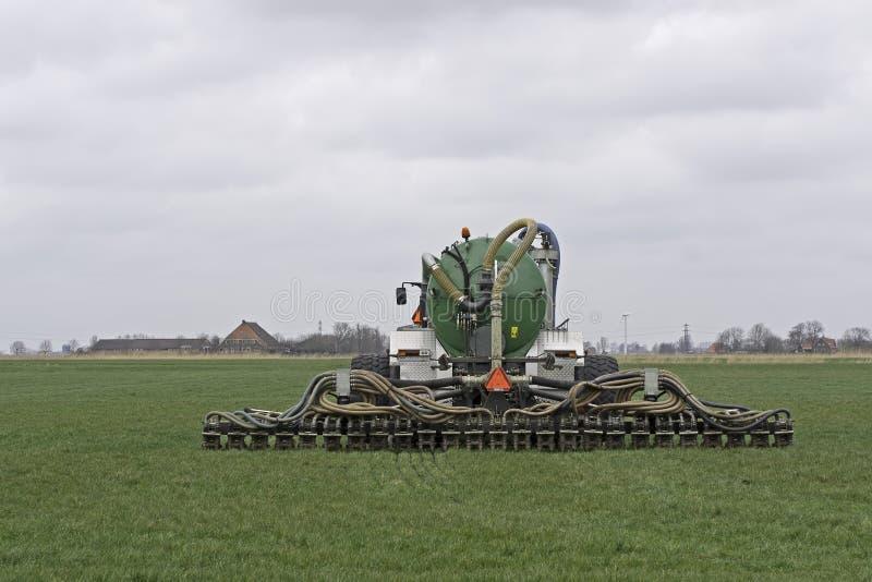 Traktor spritzt Jauche auf einem Gebiet ein lizenzfreie stockfotos