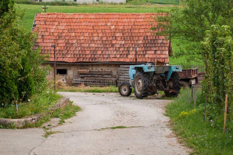 Traktor und Haus auf dem Berg lizenzfreies stockbild