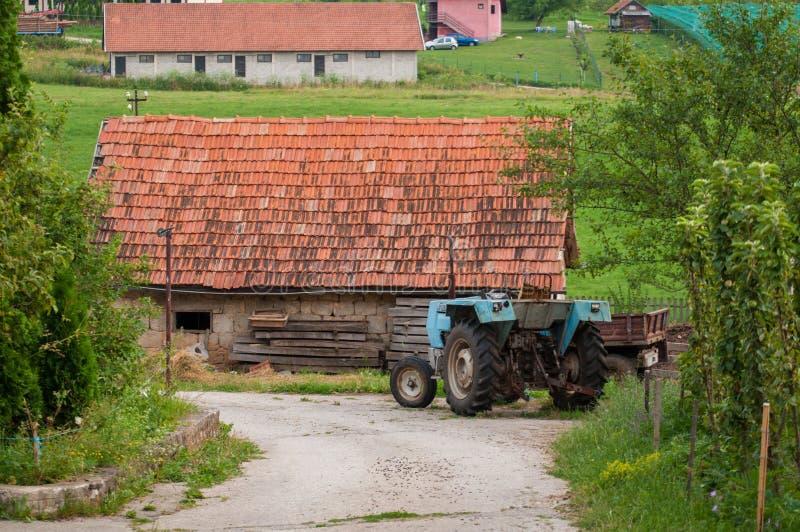 Traktor und Haus auf dem Berg lizenzfreies stockfoto