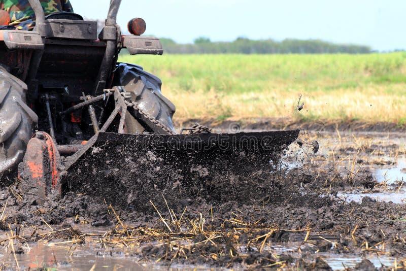 Traktorbewegungen durch ein nass Pfützenschlammschwarzes, -traktor, der am Reisfeld pflügen und -spritzen von schlammigem nass, S stockfoto