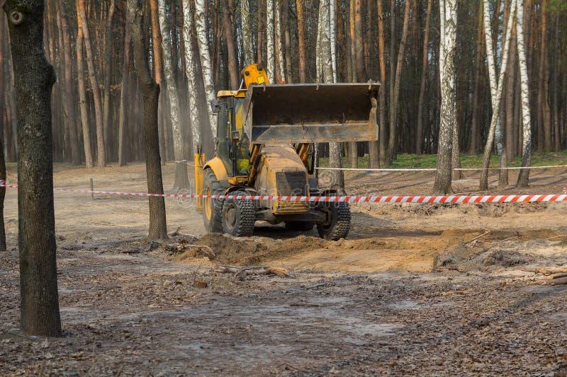 Traktoren gräver jordningen i skogområdet arkivfoto