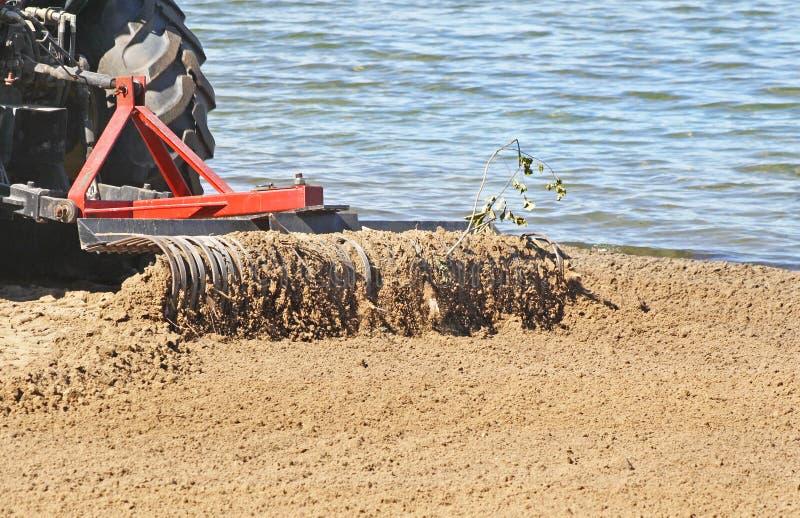 Traktoren med stor metall krattar fäst sikta, att kratta och att göra klar skräp på en offentlig strand i otta arkivbild