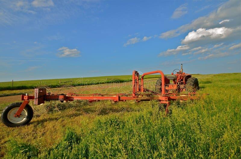 Traktoren och krattar parkerat i Hay Field fotografering för bildbyråer