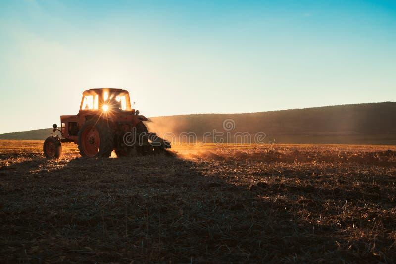 Traktoren som odlar fältet på våren, soluppsättningar, gryr behint kullarna arkivfoto