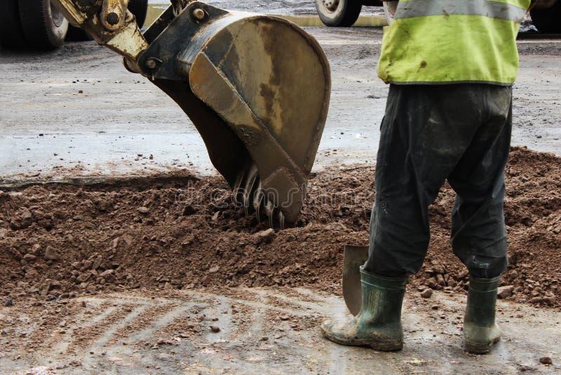 Traktoren tar bort delen av jorden med en hink, innan den asfalterar vägen för att lappa Ordföranden av byggmästareställningssida royaltyfria foton
