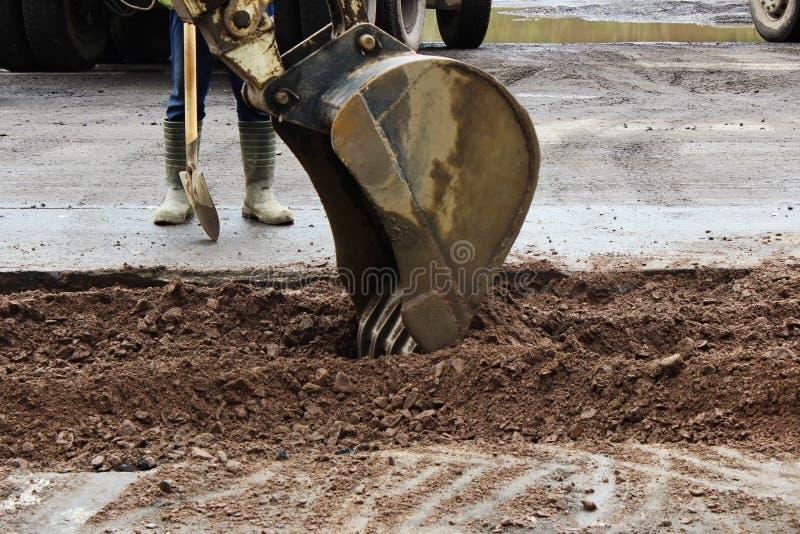 Traktoren tar bort delen av jorden med en hink, innan den asfalterar vägen för att lappa Ordföranden av byggmästareställningssida arkivfoto