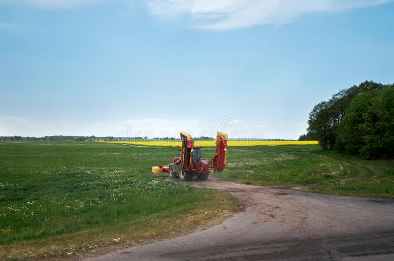 _ Traktoren tar bort våldtar i fälten av Vitryssland Maj 23, 2017 fotografering för bildbyråer