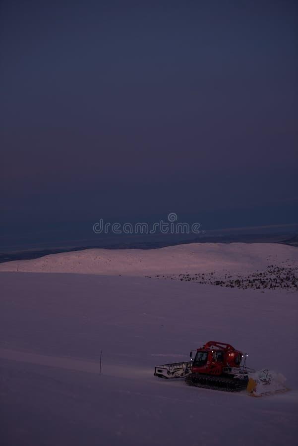 Traktorlokalvårdsnö på skida sluttar i fjällängarna arkivbild