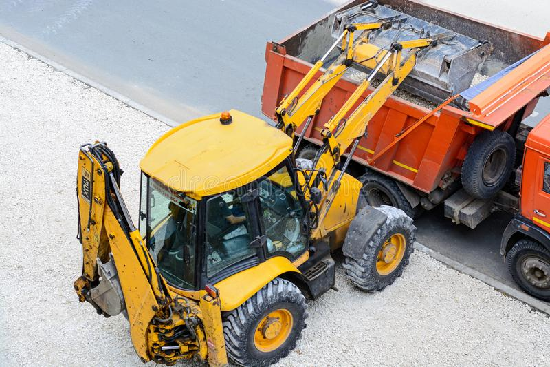 Traktorpäfyllningsgrus in i en lastbil arbeten för väg för konstruktionsdikeinstallation royaltyfria foton