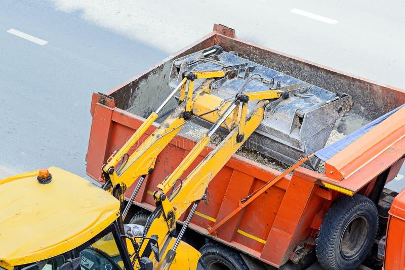 Traktorpäfyllningsgrus in i en lastbil arbeten för väg för konstruktionsdikeinstallation fotografering för bildbyråer