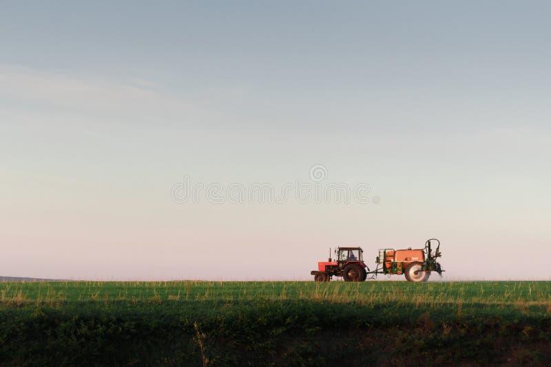 Traktorsprühschädlingsbekämpfungsmittel auf Feld mit Sprüher bei Sonnenuntergang stockfoto