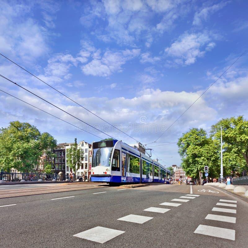 Tram d'avvicinamento nel centro urbano di Amsterdam, Paesi Bassi fotografia stock libera da diritti