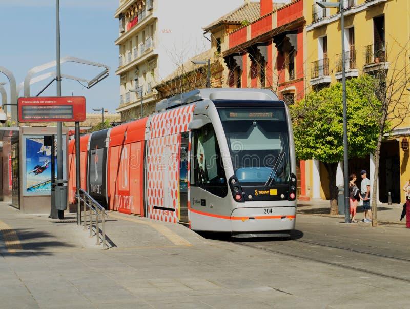Tram, die am Tram-Halt in Sevilla, Spanien, mit Touristen im Hintergrund wartet stockfotos