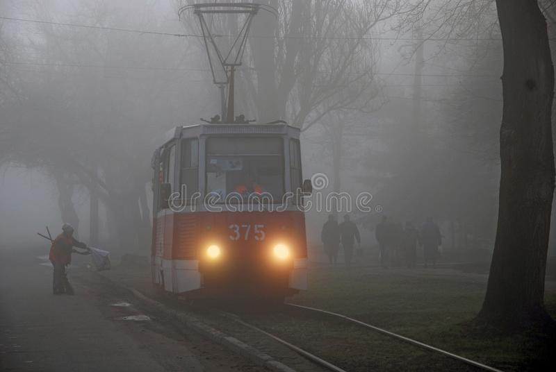 Tram in the fog,. People in the fog go to work, the janitor cleans the way, tram lights are on, the rails are wet after the fog, the morning mist closes the royalty free stock photo