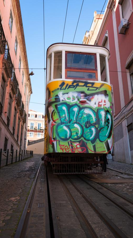Tram with graffiti in narrow steep street in Lisbon stock images