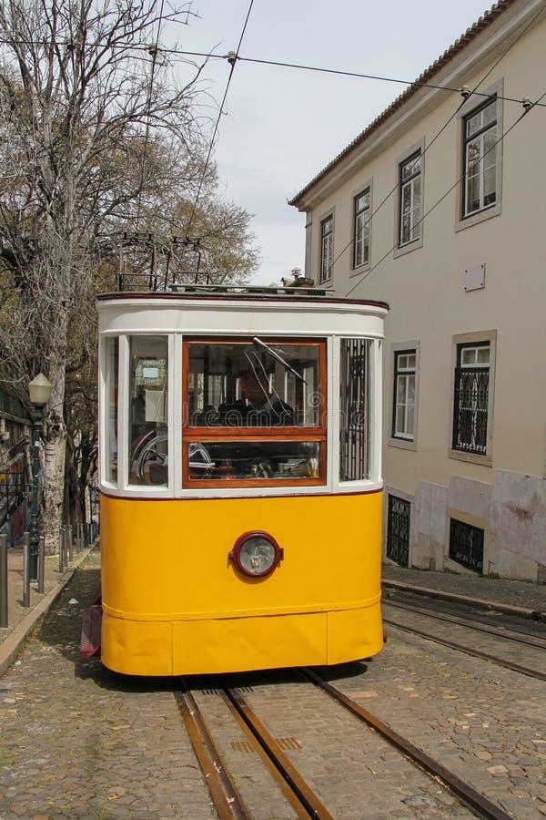 Tram jaune célèbre sur la rue étroite à Lisbonne, Portugal photos stock