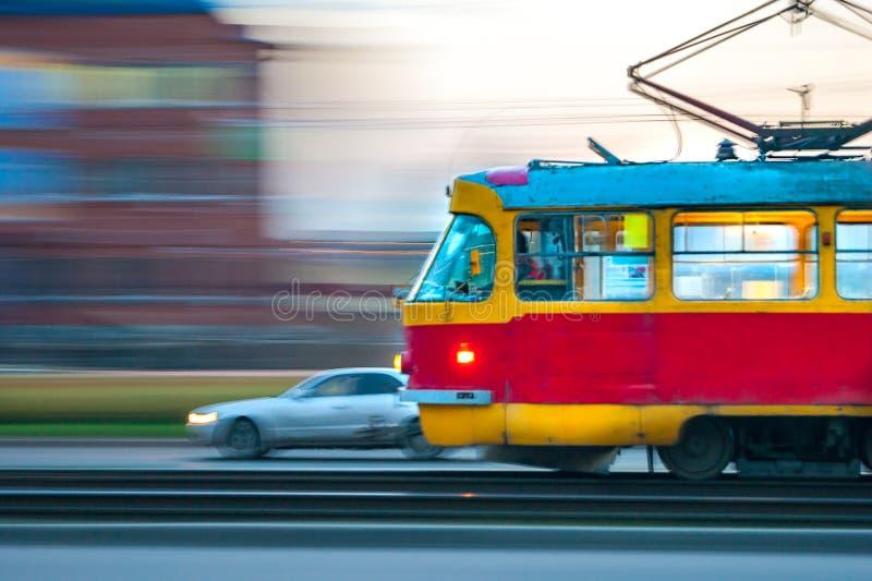 Tram rouge et jaune rapide dans la ville avec des lumières dessus images libres de droits
