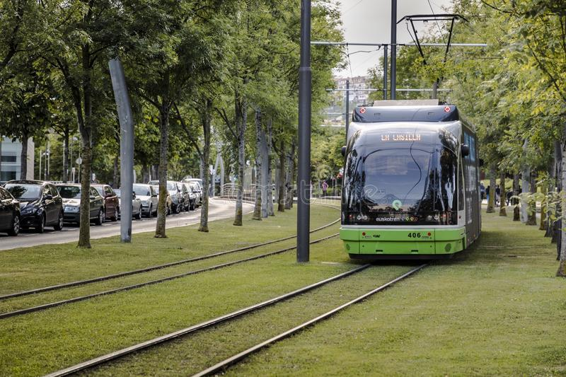 The tram runs through the city center on tracks surrounded by grass. The modern tram of the city of Bilbao circulates around the Guggenheim museum, through a stock photos